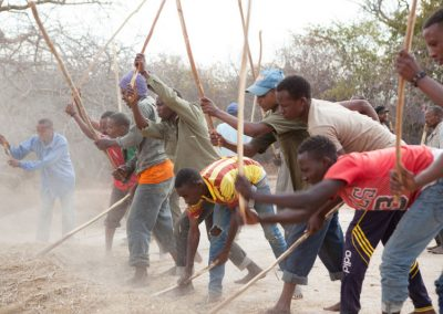 Threshing the Sorghum brings the community together.